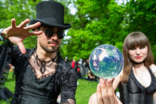 A man and a woman looking into a mirrorball attend the traditional park picnic on the first day of the annual Wave-Gotik Treffen, or Wave and Goth Festival, on May 17, 2013 in Leipzig, Germany. The four-day festival, in which elaborate fashion is a must, brings together over 20,000 Wave, Goth and steam punk enthusiasts from all over the world for concerts, readings, films, a Middle Ages market and workshops. (Photo by Marco Prosch)