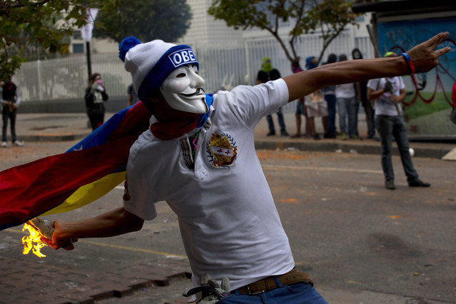 Venezuela: An anti-government protester wearing a Guy Fawkes mask throws a molotov cocktail at the Bolivarian National Police during clashes in Caracas, Venezuela, Thursday, April 17, 2014. Opposition protesters have been demonstrating against high crime, high inflation and shortages of basic goods since mid-February. (Photo by Ramon Espinosa/AP Photo)