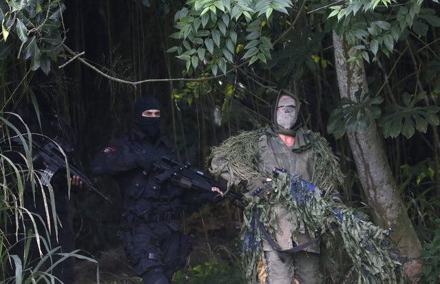 Members of the Brazilian Navy take on the role of snipers during an exhibition showcasing their operational capacity to combat terrorist attacks and riots, ahead of the FIFA Confederations Cup and World Youth Day in Rio de Janeiro on May 27, 2013. (Photo by Ricardo Moraes/Reuters)
