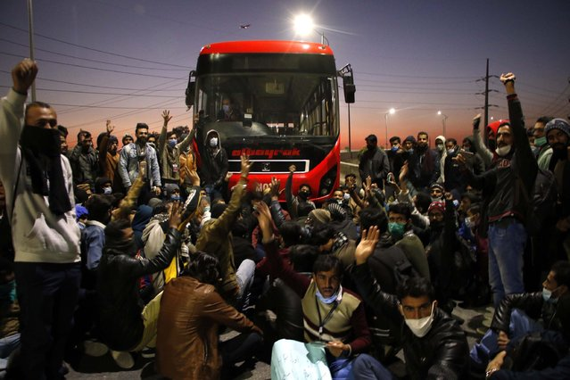 Ticketing staff of Metro rapid transit bus service shout slogans as they block the bus route to protest against the non-payment of their wages, in Islamabad, Pakistan, 26 November 2020. (Photo by Sohail Shahzad/EPA/EFE/Rex Features/Shutterstock)