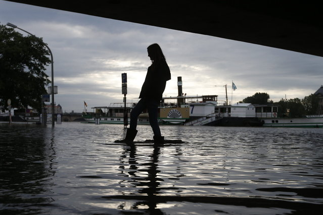 A woman with rubber boots walks across a flooded street under a bridge in Dresden, Germany, Monday, June 3, 2013. Heavy rainfalls cause flooding along rivers and lakes in Germany, Austria, Switzerland and the Czech Republic. (Photo by Markus Schreiber/AP Photo)