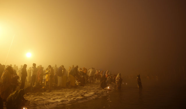 "Hindu devotees bathe early morning at Sangam, the confluence of rivers Ganges and Yamuna, to mark Makar Sankranti festival during the annual traditional fair of ""Magh Mela"" in Allahabad, India, Wednesday, January 14, 2015. Hundreds of thousands of devout Hindus are expected to take holy dips at the confluence during the astronomically auspicious period of over 45 days celebrated as Magh Mela. (Photo by Rajesh Kumar Singh/AP Photo)"
