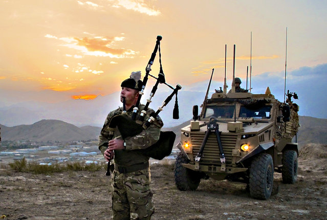Ministry of Defence handout photo of Corporal Kevin Glover (28) from Palnacki, Dumfries and Galloway, piping outside the battalion s base at Camp Qargha to celebrate St Andrew's Day Monday, November 30, 2015. (Photo by PA Wire/Ministry of Defence)