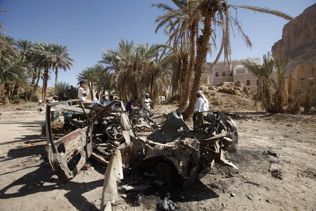 People gather near the wreckage of a car destroyed by a U.S. drone air strike that targeted suspected al Qaeda militants in August 2012, in the al-Qatn district of the southeastern Yemeni province of Hadhramout February 5, 2013. (Photo by Khaled Abdullah/Reuters)