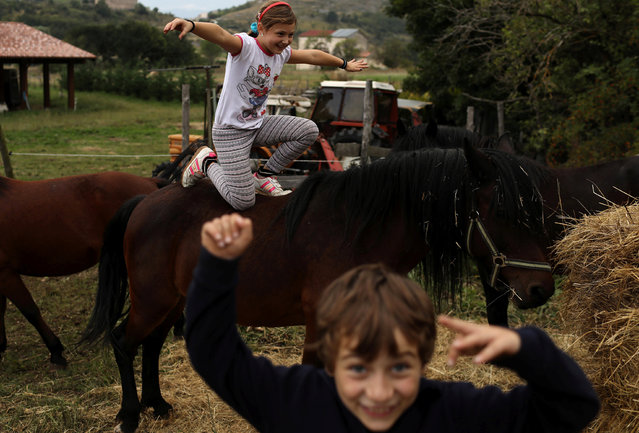 Ginevra, 10, and her brother Giulio Cesare, 7, play with their horses at the family farm in the town of Santo Stefano di Sessanio in the province of L'Aquila in Abruzzo, inside the national park of the Gran Sasso e Monti della Laga, Italy, September 13, 2016. (Photo by Siegfried Modola/Reuters)