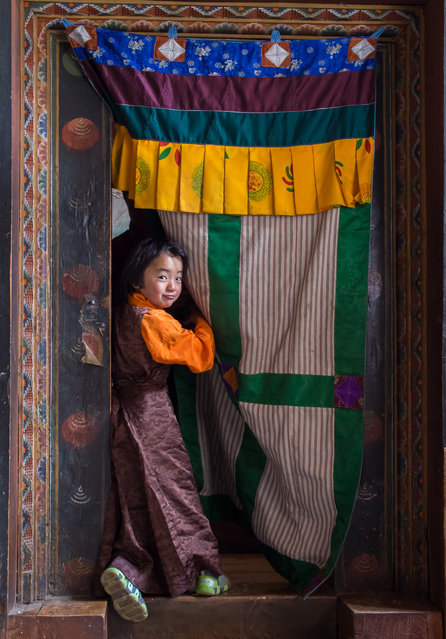 """""""Girl at the door"""". I found this girl in a monastery in Jakar, posing at the door of the main entrance to the chapel. Location: Jakar, Bhutan. (Photo and caption by Juan Abal Lopez/National Geographic Traveler Photo Contest)"""
