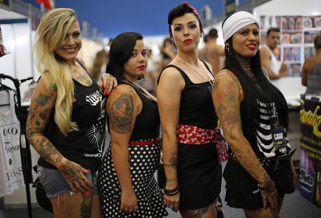 Women sporting tattoos pose for the press during Rio Tattoo Week in Rio de Janeiro, Brazil, Friday, January 16, 2015. (Photo by Silvia Izquierdo/AP Photo)
