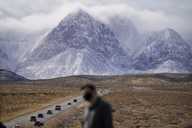 People look at mountains recently covered with snow, Monday, January 25, 2021, at the Red Rock National Conservation Area near Las Vegas. (Photo by John Locher/AP Photo)