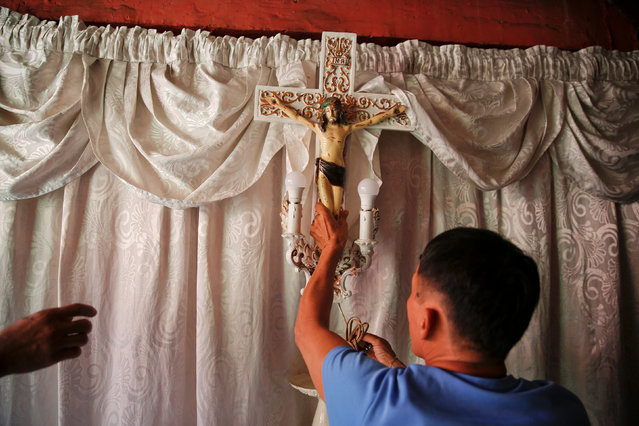 A crucifix is taken down from a room where the coffin of Florjohn P. Cruz was placed as his remains are taken for funeral in Manila, Philippines October 30, 2016. Florjohn P. Cruz was killed in a police drugs buy bust operation. (Photo by Damir Sagolj/Reuters)
