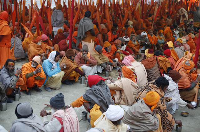 Indian Sadhus, or Hindu holy men, participate in a community feast at the Sangam, the confluence of the Rivers Ganges, Yamuna and mythical Saraswati, during the annual month-long Magh Mela religious fair in Allahabad, India, Friday, January 16, 2015. Hundreds of thousands of devout Hindus are expected to take holy dips at the confluence during the astronomically auspicious period of over 45 days celebrated as Magh Mela. (Photo by Rajesh Kumar Singh/AP Photo)