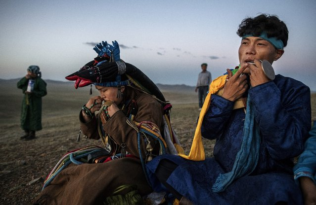 Mongolian Shamans or Buu, play the mouth harp or khel khurr, used to summon spirits, during a sun ritual ceremony to mark the period of the Summer Solstice in the grasslands at sunrise on June 22, 2018 outside Ulaanbaatar, Mongolia. (Photo by Kevin Frayer/Getty Images)
