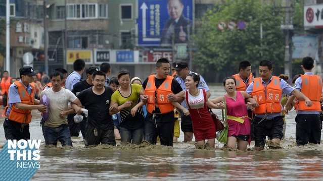 Policemen hold the arms of residents as they walk on a flooded street after heavy rainfall hit Chengdu, Sichuan province, July 9, 2013. (Photo by Reuters/Stringer)