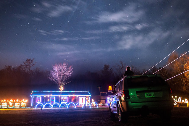 Demetri Masincup, 8,  sits on the top a car while visiting the Christmas light show in Briery Branch, Va., on Wednesday, December 16, 2015. The 35-minute long show had lights choreographed with music that played on the radio. (Photo by Austin Bachand/Daily News-Record via AP Photo)