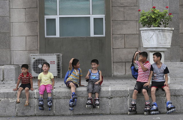 Children take a break from skating around the Kim Il Sung Square on Sunday, July 21, 2013, downtown Pyongyang, North Korea. (Photo by Wong Maye-E/AP Photo)