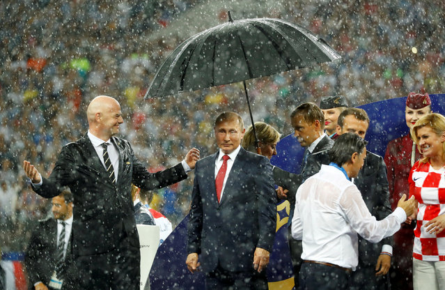 FIFA president Gianni Infantino and President of Russia Vladimir Putin during the presentation as Croatia coach Zlatko Dalic talks to President of France Emmanuel Macron and President of Croatia Kolinda Grabar-Kitarovic during the trophy ceremony after the Russia 2018 World Cup final football match between France and Croatia at the Luzhniki Stadium in Moscow on July 15, 2018. (Photo by Kai Pfaffenbach/Reuters)
