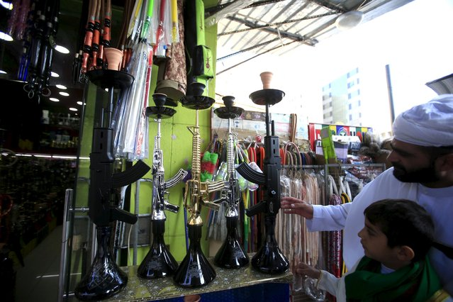 People inspect hookahs shaped like rifles on display for sale in a souk at the port city of Sidon, southern Lebanon, December 23, 2015. (Photo by Ali Hashisho/Reuters)