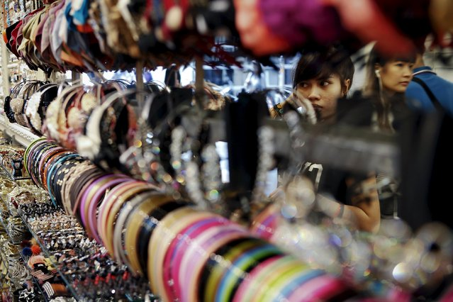 A woman tries on fashion accessories at a shopping mall in central Bangkok in this April 12, 2013 file photo. Thailand's central bank kept its key interest rate unchanged on December 16, 2015, as expected, leaving fiscal stimulus and government spending to support the weak domestic economy, which it now expects to perform slightly better than forecast. (Photo by Damir Sagolj/Reuters)