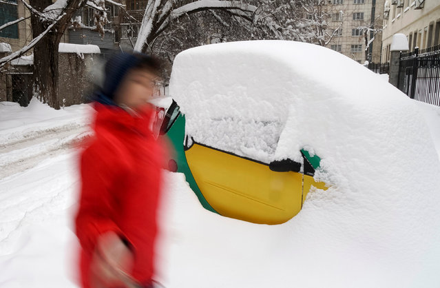 A boy walks past a snow covered car after a heavy snowfall in Almaty, Kazakhstan, November 20, 2016. (Photo by Shamil Zhumatov/Reuters)