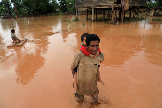 A man carries his child during the flood after the Xepian-Xe Nam Noy hydropower dam collapsed in Attapeu province, Laos, July 26, 2018. (Photo by Soe Zeya Tun/Reuters)