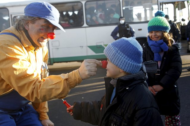 A member of Red Noses Clowndoctors entertains migrants before their departure to Austria at a registration center in Dobova, Slovenia, December 27, 2015. (Photo by Srdjan Zivulovic/Reuters)
