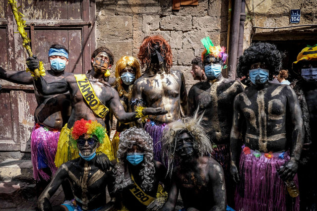 Carnival participants dressed in costume and wearing body paint pose for a group picture during the annual Zambo carnival held in Lebanon's northern city of Tripoli on March 14, 2021, marking the last period of excess on the eve of the Christian Greek Orthodox lent. The inspiration of the annual Zambo celebration is unclear, despite it being a tradition that stretches back over a century to when an emigrant to Brazil returned to his native Tripoli bringing the carnival with him. (Photo by Ibrahim Chalhoub/AFP Photo)
