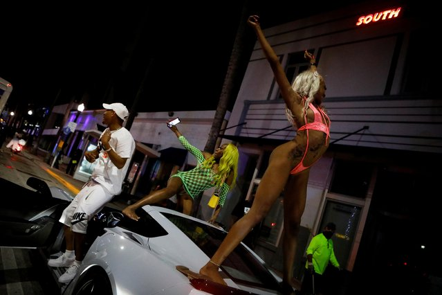 Women dance on top of a car as revelers enjoy spring break festivities despite an 8pm curfew imposed by local authorities, amid the coronavirus disease (COVID-19) pandemic, in Miami Beach, Florida, U.S., March 20, 2021. (Photo by Marco Bello/Reuters)