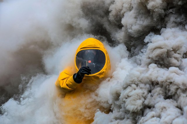 An armed policeman moves through a simulated contamination area during a drill on March 19, 2021 in Guangzhou, Guangdong Province of China. (Photo by Yan Yicheng/VCG via Getty Images)