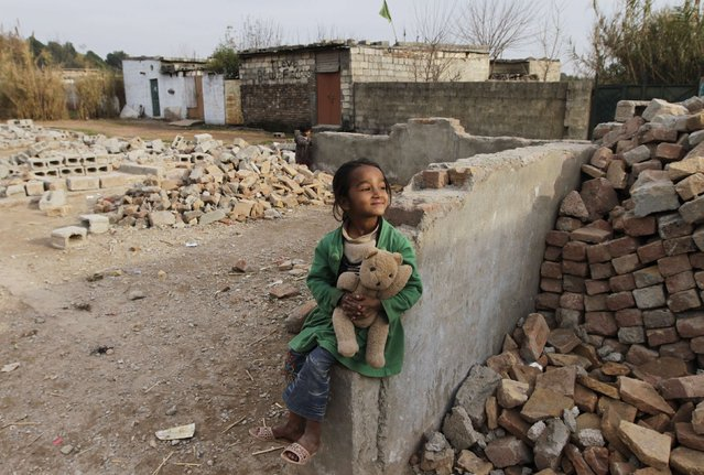 A girl holds a stuffed toy while sitting on a broken wall near her family house at a slum on the outskirts of Islamabad February 6, 2015. (Photo by Faisal Mahmood/Reuters)