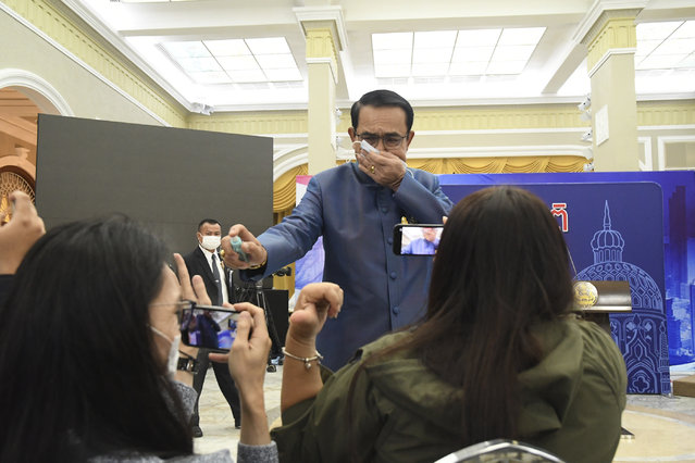 Thailand's Prime Minister Prayuth Chan-ocha sprays alcohol mist on a front row of reporters sitting inside the press conference room at Government house in Bangkok, Thailand, Tuesday, March 9 , 2021. Riled by a final question about a possible Cabinet reshuffle, the prime minister told reporters to mind their own business, then grabbed a container of alcohol mist and doused the front row before sauntering off. (Photo by AP Photo/Stringer)