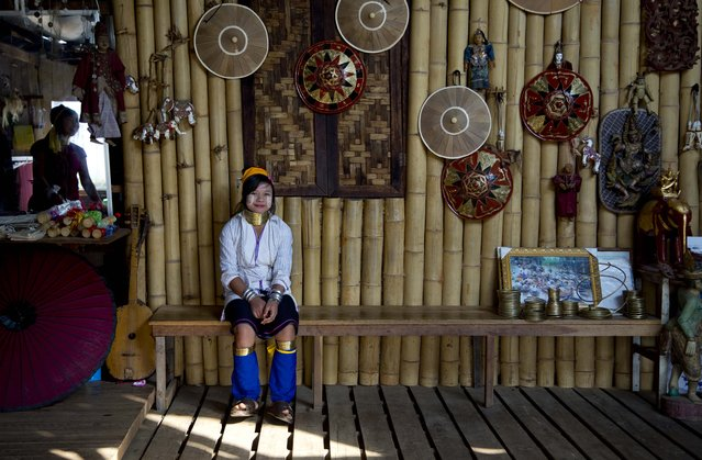 An ethnic Kayan-Padaung girl in traditional attire awaits for tourists at a souvenir shop in Ywama village, Inle Lake, northeastern Shan state, Myanmar, Monday, February 16, 2015. Wearing neck-rings is officially discouraged in Myanmar but shop owners employ Padang women in traditional attire as a tourist attraction. (Photo by Gemunu Amarasinghe/AP Photo)