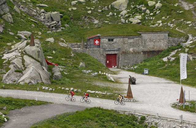 Cyclists ride past the Hotel La Claustra located in a former bunker of the Swiss army on the St. Gotthard mountain pass, Switzerland August 8, 2014. (Photo by Arnd Wiegmann/Reuters)