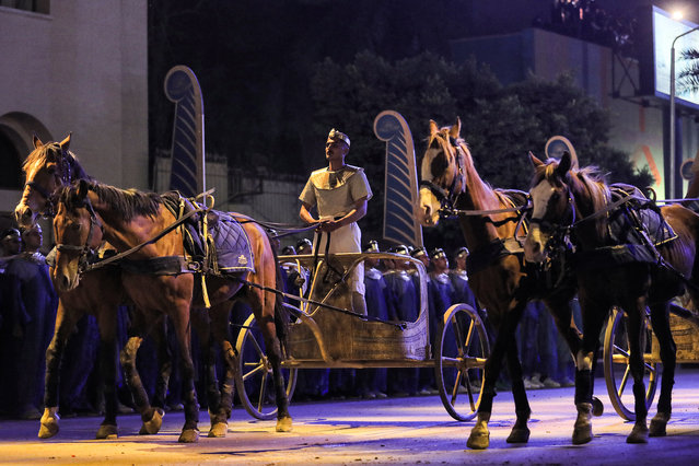 A performer rides a two-horse chariot at the start of the parade of 22 ancient Egyptian royal mummies departing from the Egyptian Museum in Cairo's Tahrir Square on April 3, 2021, on their way to their new resting place at the new National Museum of Egyptian Civilisation (NMEC) about seven kilometres south in historic Fustat (Old Cairo). Dubbed the Pharaohs' Golden Parade, the 18 kings and four queens will travel in order, oldest first, each aboard a separate float decorated in ancient Egyptian style. (Photo by Mahmoud Khaled/AFP Photo)
