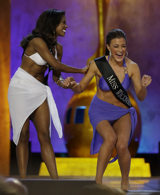 Miss Wisconsin Paula Mae Kuiper, right, reacts after finding out she's advancing beyond the lifestyle round as Miss Texas Ivana Hall congratulates her during the Miss America 2014 pageant, Sunday, September 15, 2013, in Atlantic City, N.J. (Photo by Mel Evans/AP Photo)