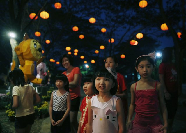 Children look at a light display for Chinese New Year at the Fo Guang Shan Dong Zen Temple in Jenjarom, outside Kuala Lumpur, February 13, 2015. The Chinese Lunar New Year on Feb. 19 will welcome the Year of the Sheep (also known as the Year of the Goat or Ram). (Photo by Olivia Harris/Reuters)