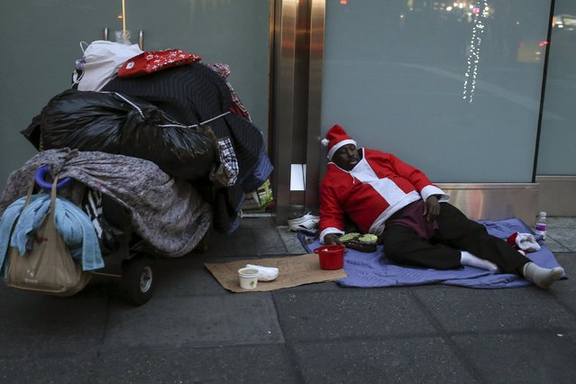 A homeless man dressed as Santa Claus sleeps on the ground during unseasonably warm weather on Christmas eve in the Manhattan borough of New York December 24, 2015. (Photo by Carlo Allegri/Reuters)