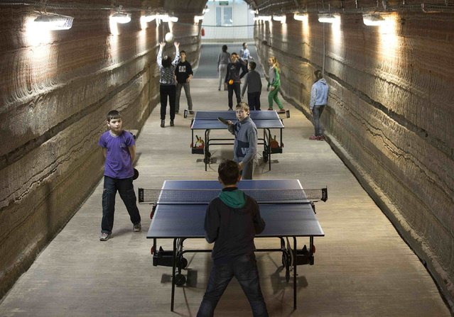 Children play table tennis in the facilities of Belarus' Republican Clinic of Speleotherapy within a salt mine, as part of their treatment, near the town of Soligorsk, south of Minsk, February 19, 2015. (Photo by Vasily Fedosenko/Reuters)
