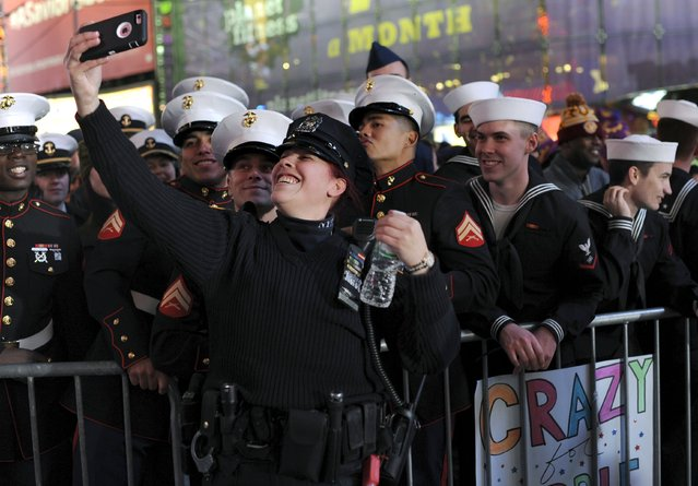 New York Police Department officer Nydia Rodriguez takes a selfie with members of the U.S. Marine Corps and U.S. Navy during New Year's celebrations in Times Square in the Manhattan borough of New York December 31, 2015. (Photo by Darren Ornitz/Reuters)
