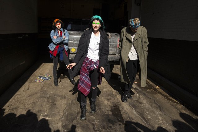 Models Maggie Laine, Hollie-May Saker and Jordan Barrett play exit a garage following the Jeremy Scott Fall/Winter 2015 collection presentation at New York Fashion Week February 18, 2015. (Photo by Andrew Kelly/Reuters)
