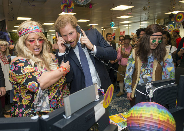 Britain's Prince Harry, centre, talks on the phone, during an ICAP Charity Trading Day in support of Sentebale – a charity supporting orphans and vulnerable children, with Amanda Hartnell, left and Dermot Doherty, in London, Wednesday, December 7, 2016. (Photo by Geoff Pugh/Pool Photo via AP Photo)