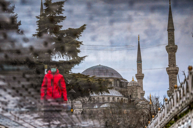 A reflection on waste liquid shows a tourist walking near the Blue mosque at the Sultanahmet Square on the first day of the Muslim fasting month of Ramadan in Istanbul on April 13, 2021. (Photo by Ozan Kose/AFP Photo)