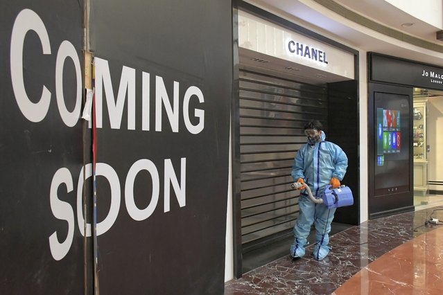 A man sanitizes the premises of a shopping mall before reopening after being closed since April as part of measures to curb the spread of coronavirus in New Delhi, India, Sunday, June 6, 2021. Businesses in two of India's largest cities are reopening as part of a phased easing of lockdown measures in several states now that the number of new coronavirus infections in the country is on a steady decline. (Photo by Ishant Chauhan/AP Photo)