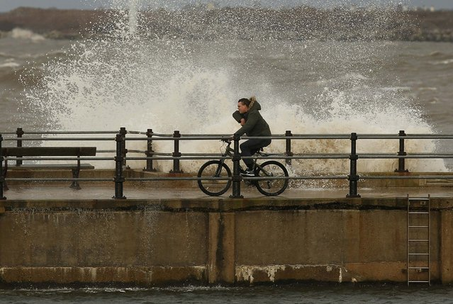 A man rides his bike as waves break over the promenade at New Brighton, near Wallasey in Britain January 26, 2016. (Photo by Phil Noble/Reuters)