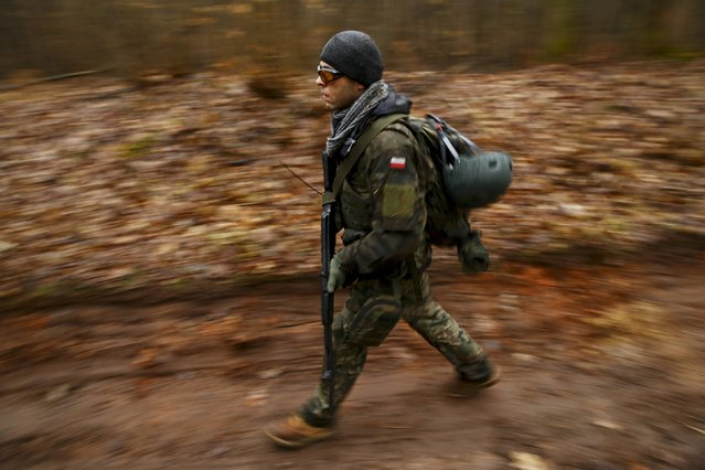 A man takes part in an endurance march during a territorial defence training organised by paramilitary group SJS Strzelec (Shooters Association) in the forest near Minsk Mazowiecki, eastern Poland March 14, 2014. (Photo by Kacper Pempel/Reuters)