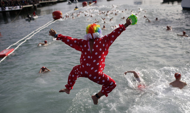 An athlete dressed as a clown jumps into the Mediterranean sea as he takes part in the Copa Nadal in the Spanish port of Barcelona in Barcelona, Spain, Sunday, December 25, 2016. The Copa Nadal (Christmas Cup) is a traditional swimming competition that takes place in Barcelona every December 25th, where participants swim 200 meters in the open sea in the port of Barcelona. (Photo by Manu Fernandez/AP Photo)