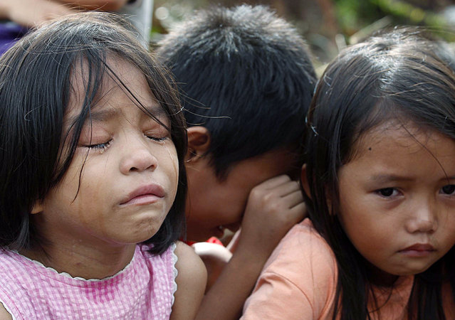 Filipino typhoon survivor children, who escaped after their village was attacked by allegedly armed men, wait for social workers in the super typhoon devastated city of Tacloban, Leyte province, Philippines, 13 November 2013. (Photo by Dennis M. Sabangan/EPA)