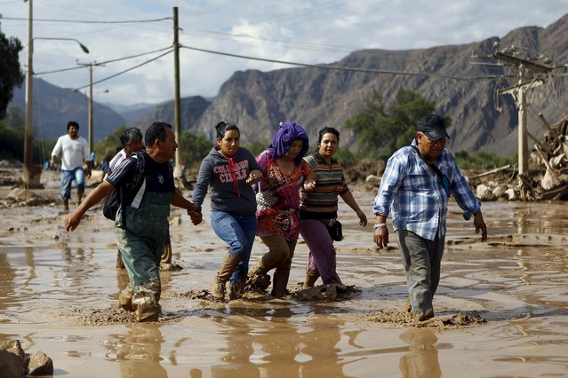 Locals cross a flooded street at Copiapo city, March 26, 2015. (Photo by Ivan Alvarado/Reuters)