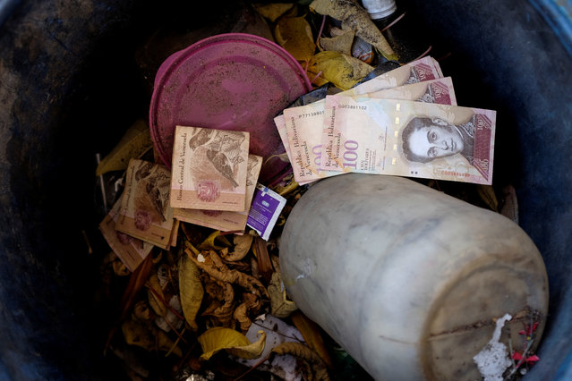 Venezuelan 100 bolivar notes thrown by people in a trash bin are seen at a gas station of the Venezuelan state-owned oil company PDVSA in Caracas, Venezuela on August 21, 2018. (Photo by Marco Bello/Reuters)