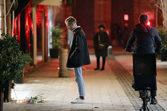 """A man pays respects to the victims the night following an attack that killed three persons and wounding at least 13, in Strasbourg, eastern France, Wednesday, December 12, 2018. More than 24 hours after a man sprayed gunfire at crowds in France's largest Christmas market as he shouted """"God is great!"""" over 700 security forces combed the eastern city of Strasbourg on Wednesday for the 29-year-old suspect who's been in trouble with the law since age 10. (Photo by Jean Francois Badias/AP Photo)"""