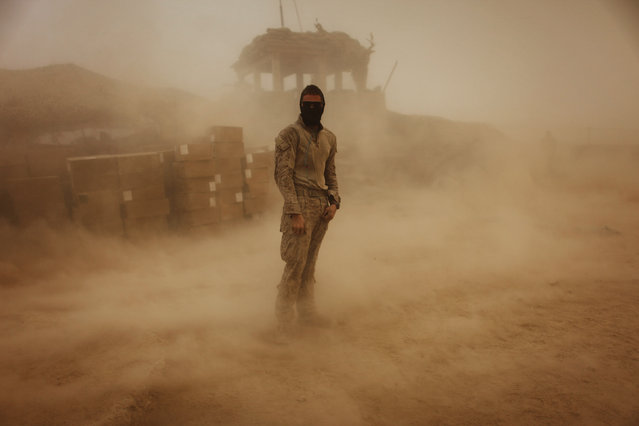 Private First Class Brandon Voris, 19, of Lebanon, Ohio, from the First Battalion Eighth Marines Alpha Company stands in the middle of his camp as a sandstorm hits his remote outpost near Kunjak in southern Afghanistan's Helmand province, October 28, 2010. (Photo by Finbarr O'Reilly/Reuters)