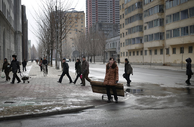 North Koreans walk down a street in downtown Pyongyang, North Korea on Sunday, February 14, 2016. (Photo by Wong Maye-E/AP Photo)